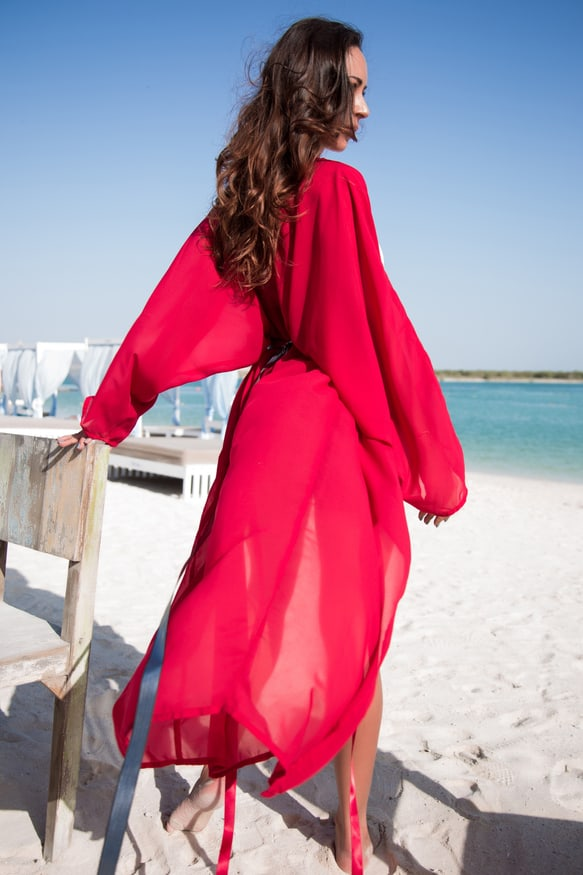 Woman in red long sleeve dress sitting on brown wooden bench